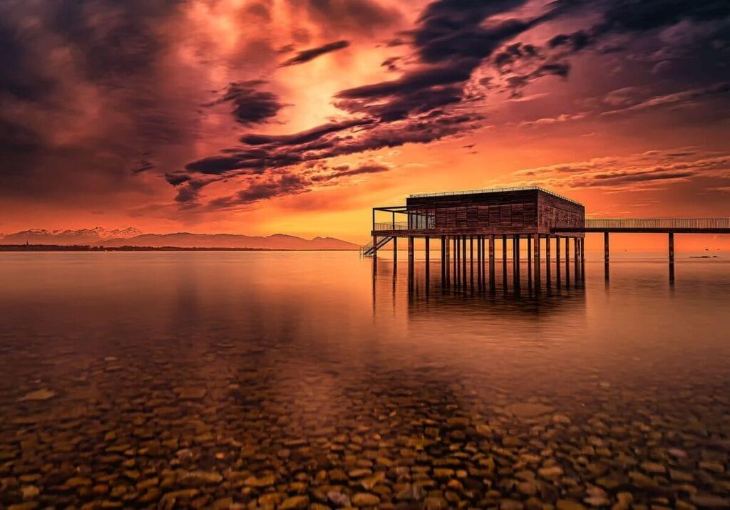 Sonnenuntergangsstimmung am Ammersee mit Steg und Holzhäuschen