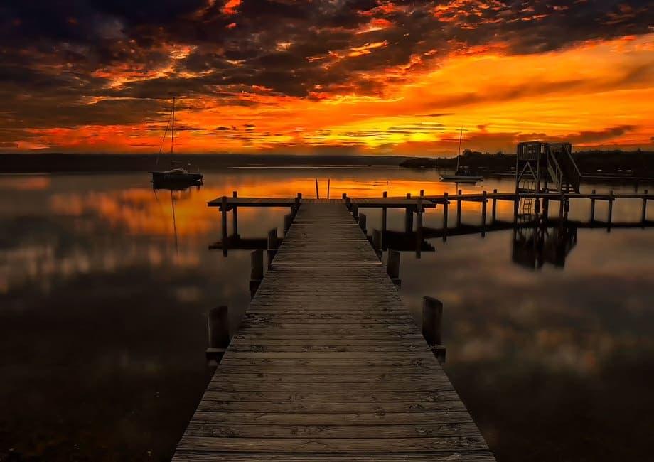 Sonnenuntergangsstimmung am Ammersee mit Steg im Vordergrund als Beispielbild für bessere Urlaubsfotos
