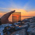 Eine Hand hält einen Filter in der Digitalfotografie in einen Sonnenuntergang