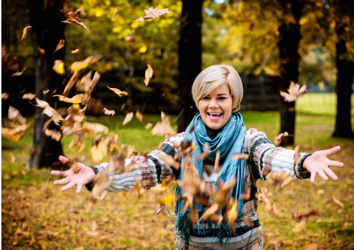 Herbstlich gefärbte Blätter von einer jungen Frau hoch geworfen als Beispiel für Fotoideen für den Herbst